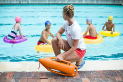 Lifeguard holding rescue can while children swimming in pool. Female lifeguard holding rescue can while children swimming in pool stock photography