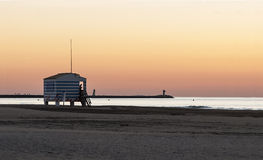 Lifeguard house on the beach. Lifeguard house during summer sunrise with calm ocean water in the background Royalty Free Stock Photo