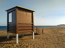 lifeguard house on the sand at a peaceful beach without guard or people swimming at the sunset hour. Behind the lifeguard station royalty free stock images