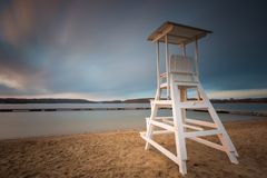Lifeguard hut on lake shore. Long exposure photo. Lake landscape with lifeguard hut. Long exposure photo with dramatic sky. Polish lake beach on Mazury lake stock photo