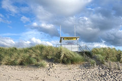 Lifeguard Hut. A vacated Lifeguard Station on situated at the dune edge on Benone Beach in Northern Ireland, UK and set against a partly cloudy and intimidating Royalty Free Stock Photo