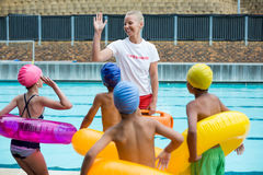 Lifeguard instructing children at poolside Stock Images