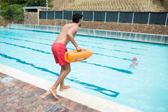 Lifeguard jumping into a swimming pool to rescue drowning boy. Rear view of lifeguard jumping into a swimming pool to rescue drowning boy Stock Photography