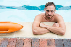 Lifeguard leaning on poolside. Portrait of lifeguard leaning on poolside Royalty Free Stock Image