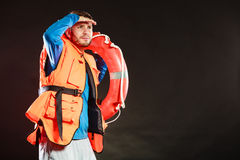 Lifeguard in life vest with ring buoy lifebuoy. Lifeguard in life vest jacket with ring buoy lifebuoy. Man supervising swimming pool water looking out in the royalty free stock images