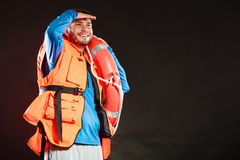 Lifeguard in life vest with ring buoy lifebuoy. Lifeguard in life vest jacket with ring buoy lifebuoy. Man supervising swimming pool water looking out in the royalty free stock image