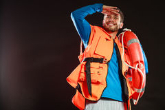 Lifeguard in life vest with ring buoy lifebuoy. Lifeguard in life vest jacket with ring buoy lifebuoy. Man supervising swimming pool water looking out in the stock images