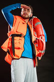 Lifeguard in life vest with ring buoy lifebuoy. Lifeguard in life vest jacket with ring buoy lifebuoy. Man supervising swimming pool water looking out in the stock photo