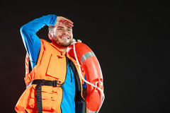 Lifeguard in life vest with ring buoy lifebuoy. Lifeguard in life vest jacket with ring buoy lifebuoy. Man supervising swimming pool water looking out in the royalty free stock photography