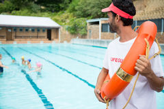 Lifeguard with lifebuoy looking at students playing in the pool. On a sunny day Stock Photos