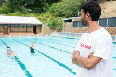 Lifeguard looking at students playing in the pool. On a sunny day Stock Images