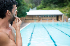 Lifeguard looking at swimming pool and blowing whistle Royalty Free Stock Photo