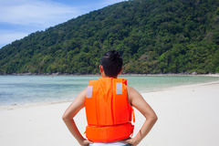 Lifeguard. A male model wearing light orange life jacket with a whistle standing on the beach acting funny by the sea royalty free stock photo