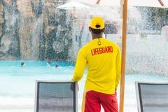 Lifeguard man wearing yellow lifeguard shirt and cap, standing o Stock Images
