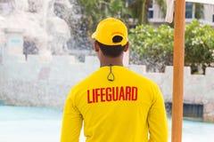 Lifeguard man wearing yellow lifeguard shirt and cap, standing o Royalty Free Stock Photos