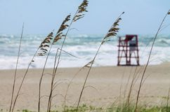 Lifeguard Not on Duty. Empty lifeguard stand, surrounded by sea oats, sand and rough seas Stock Image
