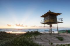 Lifeguard patrol tower on the beach at sunrise, Gold Coast Australia. Lifeguard patrol tower on the beach with clear sky at sunrise, Gold Coast Australia stock photo