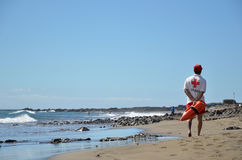 Lifeguard patrolling the beach. SAN AUGUSTIN, GRAN CANARIA, SPAIN, FEBRUARY 16, 2015: A red cross lifeguard is patrolling the beach at the resort San Augustin at Royalty Free Stock Photography
