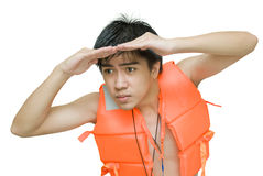 Lifeguard peering worried. Teenage Asian lifeguard with red life or swimming jacket on the lookout, peering and watching intensely in the distance sideways with Royalty Free Stock Images