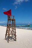 Lifeguard Post at Perfect Caribbean Beach. Empty lifeguard post with a red flag at a white, Caribbean beach under a clear sky royalty free stock photo