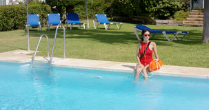 Lifeguard in red swimsuit sitting at edge of pool Royalty Free Stock Images