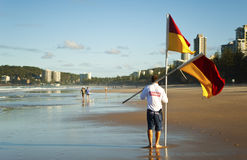 Lifeguard removing safety flags stock photography