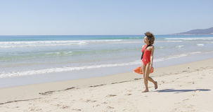 Lifeguard with rescue float walking along beach Royalty Free Stock Photos