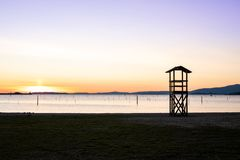 Lifeguard rescue tower on beach at sunset royalty free stock image