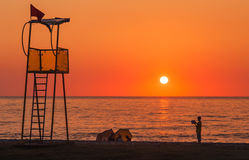 Lifeguard rescue tower on sea beach at sunset and child. With book stock photography