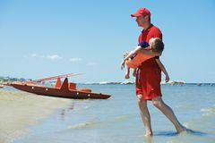 Lifeguard and rescued child. Lifeguard men with rescued child from drowning on a sea beach Stock Images