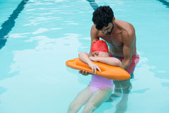 Lifeguard rescuing girl from swimming pool Stock Photos