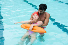 Lifeguard rescuing girl from swimming pool Royalty Free Stock Image