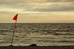 A lifeguard`s flag in the afternoon light of an overcast beach. royalty free stock photos