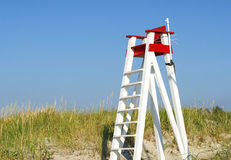 Lifeguard's seat. An empty wooden beach lifeguard's seat against a blue sky royalty free stock images