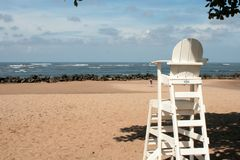Lifeguard seat upon rocky beach. A white lifeguard seat upon a rocky beach at the pacific ocean at daylight stock image