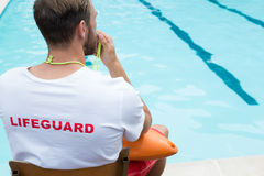 Lifeguard sitting on chair and blowing whistle at poolside. Rear view of lifeguard sitting on chair and blowing whistle at poolside Stock Photos