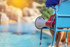 Lifeguard sitting on chair with megaphone at poolside for guarding lives.  royalty free stock photo