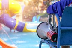 Lifeguard sitting on chair with megaphone at poolside for guarding lives royalty free stock photography