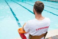 Lifeguard sitting on chair with rescue buoy at poolside Stock Photography