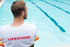 Lifeguard sitting on chair with rescue buoy at poolside Royalty Free Stock Photo