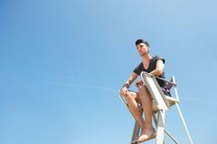 Lifeguard sitting on elevated chair Royalty Free Stock Image