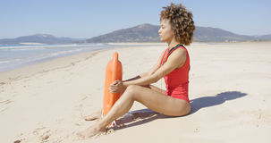 Lifeguard sitting with rescue float on beach Stock Photos