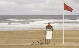 A lifeguard sitting on surveillance tower, front of the sea stock photography