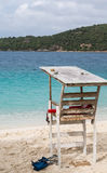Lifeguard Stand by Blue Water. Old wood lifeguard stand on beach by blue water royalty free stock photography