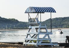 Lifeguard stand with a cover looking over the bay. A white lifeguard stand with a blue and whte striped cover at a beach on tne north shore of long island royalty free stock photography