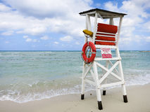 Lifeguard stand at resort on the ocean. Lifeguard stand overlooking the ocean and waves with a blue skies dotted by clouds Royalty Free Stock Image