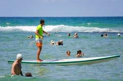 Lifeguard stand up paddling among swimmers Royalty Free Stock Image