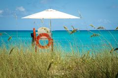Lifeguard stand with white umbrella and orange bouy on beach in Turks and Caicos islands. Lifeguard stand with white umbrella and orange bouy amidst sea oats on royalty free stock image