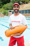 Lifeguard standing with rescue buoy near poolside. Portrait of lifeguard standing with rescue buoy near poolside Stock Photos
