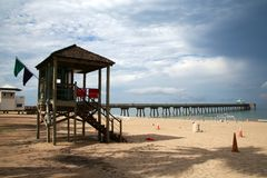 Lifeguard Station at Deerfield Beach Pier. This is the south side of Deerfield Beach, Florida with a lifeguard station to the left. Orange cones are in the sand stock image